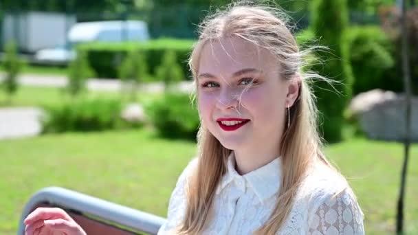 Video šťastné kavkazské blondýny dívka usmívající se do kamery.