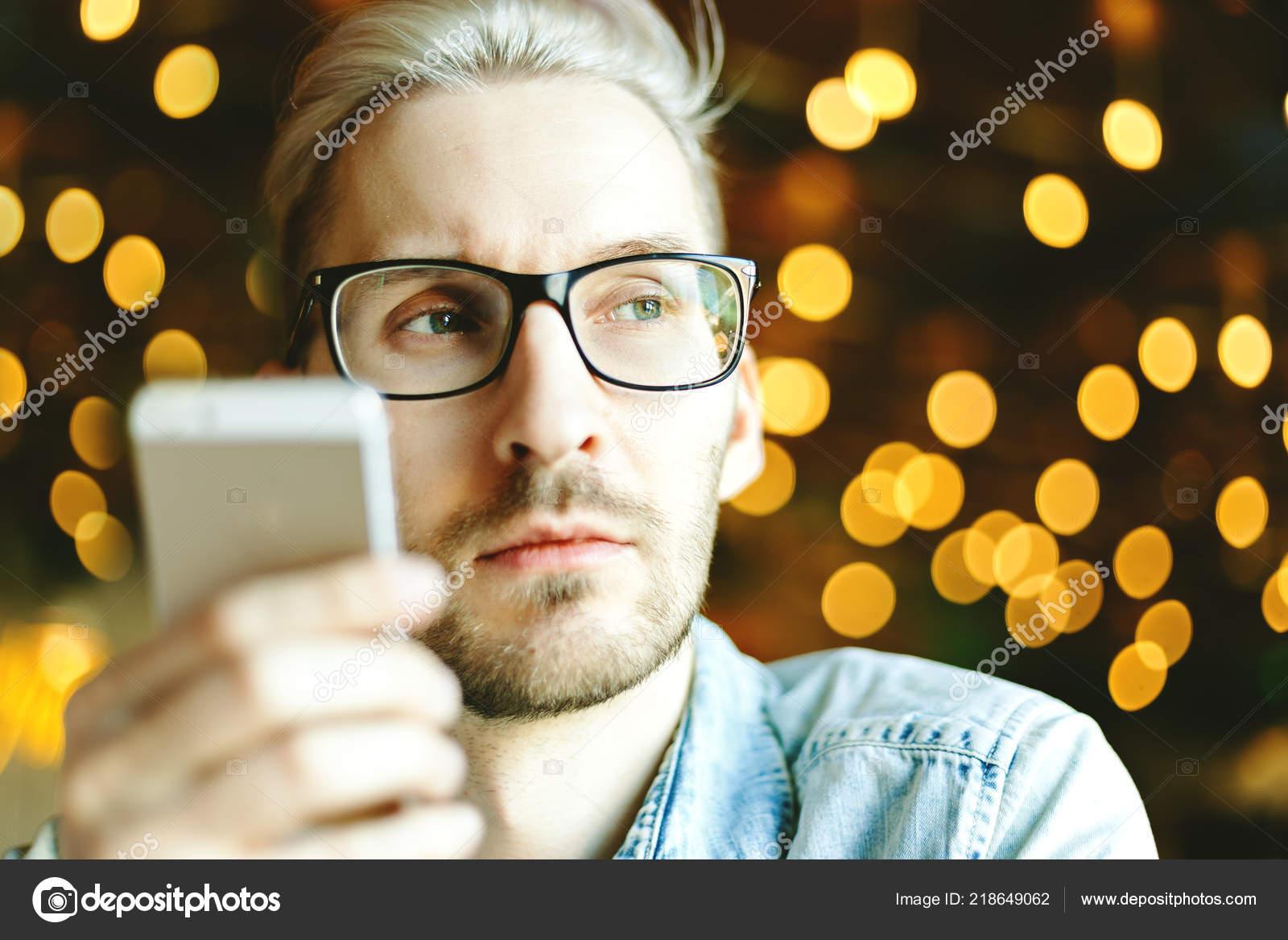 a2bdb0ff46 Hombre Joven Pensativo Anteojos Mirando Lejos Con Celular Mano Fondo — Foto  de Stock