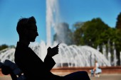 Fotografie Side view of dark male figure sitting on park bench and looking at mobile phone with bright sunlit fountain on blurred background at summer