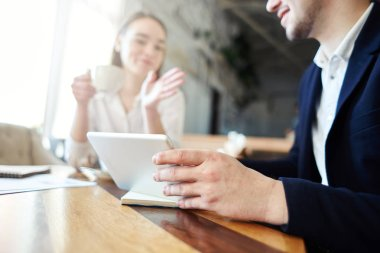 Unrecognizable businessman showing presentation on tablet computer to female business partner during coffee meeting in cafe