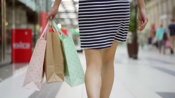 Sledovat záběr anonymní dívka procházky v nákupní centrum černý pátek a nošení nákupní tašky ve zpomaleném záběru