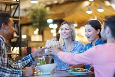 Happy four young friends toasting during festive dinner in restaurant