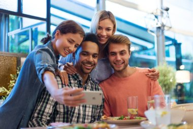 Portrait of four cheerful young friends taking selfie together on smartphone during dinner in cafe