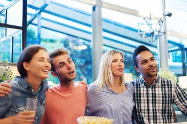Four cheerful young friends embracing while posing together for photo at table in restaurant
