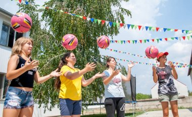 Girls, simultaneously throwing the ball in a circle in a sports game, team building
