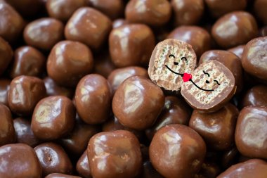 A lot of chocolate candies and one of them cutted on two halves symbolazing lovers. Imaging love. Concept of sweet love
