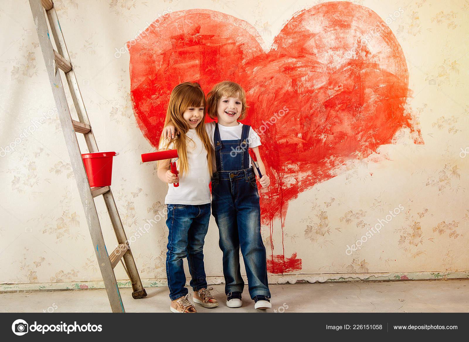 Enfants Ont Peint Le Papier Peint Dans La Chambre Avec De La Peinture Rouge.  Peindre Les Murs Avec Un Rouleau. Une Fille Et Un Garçon Peint Un Coeur Sur  Le ...