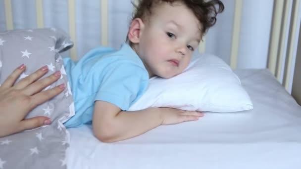 das Kind schläft in der Krippe ein, gähnt, dreht sich, schließt die Augen. Mutterschaft. Kindheit. Gesunder Schlaf.