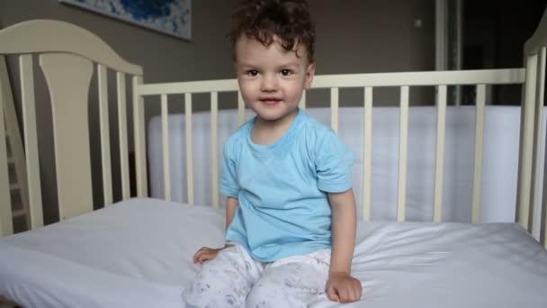 pranks. baby boy swinging on a crib. Rocking the crib. Emotions and joy. Morning waking up