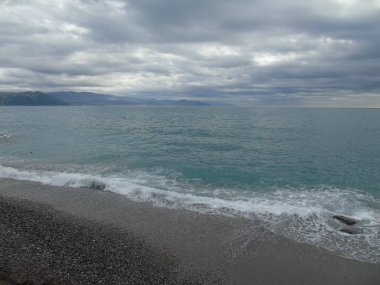 Walking around the seaside of Portofino  in Liguria with a grey sky, some green trees and some beautiful  waves