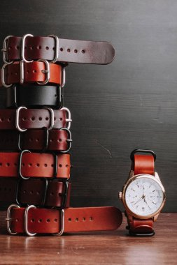 leather belts on wooden table with wristwatch