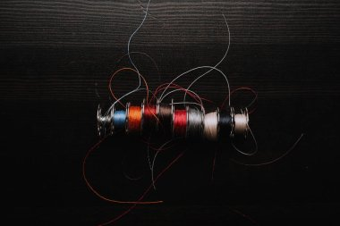 top view of sewing machine threads coils on wooden table surface, horizontal image