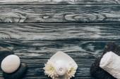 pohled shora uspořádány ručníky, oblázky, svíčka a chrysanthemum květiny pro spa a masáže na dřevěné pozadí