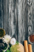 Photo top view of arranged pebbles, oil, salt and bamboo sticks for spa and massage on wooden background
