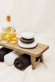 Fotografie zblízka pohled uspořádání lázeňské léčby příslušenství s ručníky, ropa a oblázky na bílém pozadí