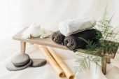 Fotografie close up view of arrangement of spa treatment accessories with towels and pebbles on white background