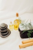 Fotografie close up view of arrangement of spa treatment accessories with towels, pebbles and essential oil on white background