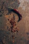 Fényképek felülnézet chili pelyhek és chili paprika, szutykos asztalon