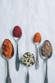 Fotografie elevated view of different spices in spoons on white table