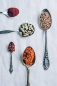 Fotografia vista superiore di coriandolo, scaglie di peperoncino e zafferano in cucchiai sulla tabella bianca