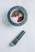Fotografie elevated view of mortar with spices and pestle on white table