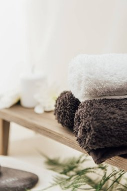 selective focus of arrangement of spa treatment accessories with towels on white background