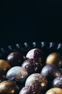 closeup view of pile of different chocolate candies in bowl on black background
