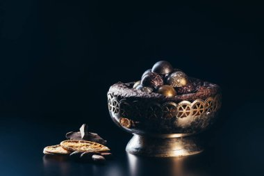 closeup view of vintage bowl with candies, chocolate pieces, nuts and dry orange slices on black background