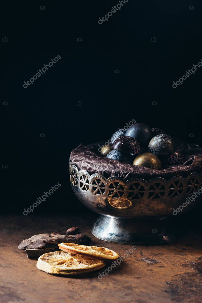 closeup view of dry orange slices, candies in vintage bowl and chocolate pieces on black background