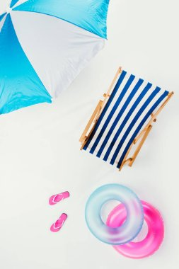 Top view of beach umbrella, striped beach chair, flip flops and inflatable rings isolated on white stock vector