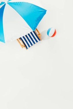 Top view of beach umbrella, striped beach chair and inflatable beach ball isolated on white stock vector