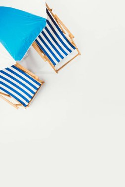 top view of beach umbrella and striped beach chairs isolated on white