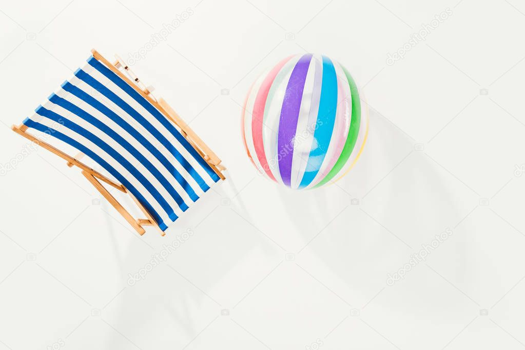 top view of striped beach chair and inflatable ball isolated on white