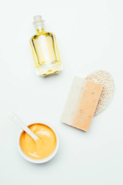 flat lay with orange clay mask in container, spoon, sponge, soap and perfume bottle isolated on white surface