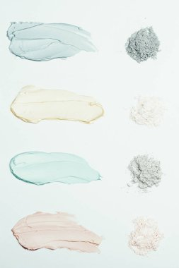 flat lay with clay powder and four colorful clay mask smudges placed in row isolated on white surface