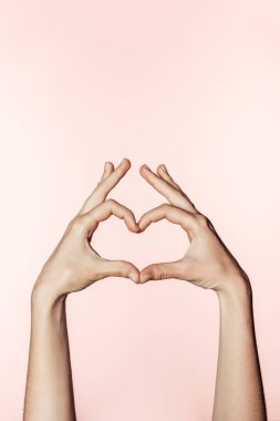 partial view of woman doing heart symbol by fingers isolated on pink background