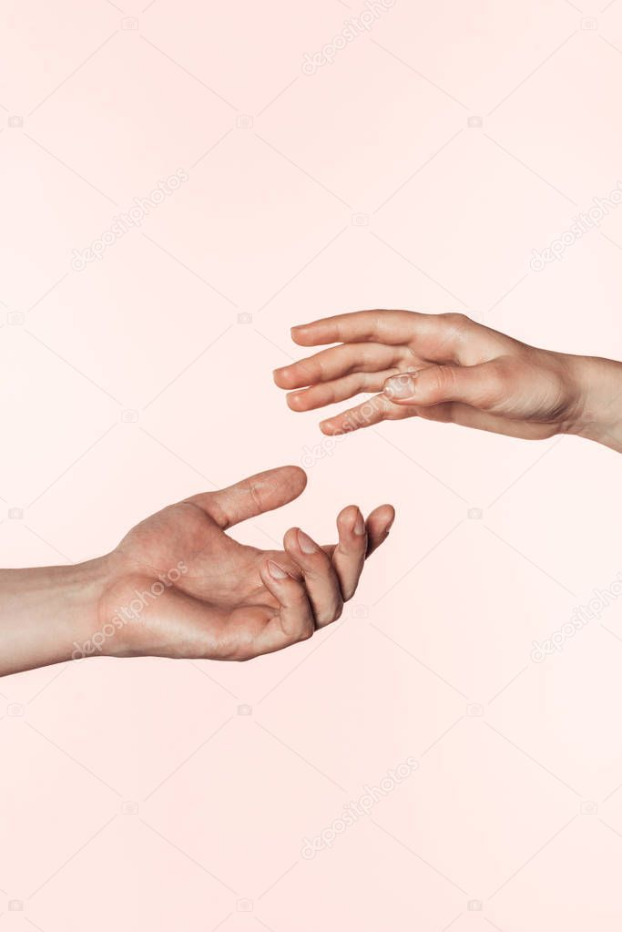 Partial view of woman and man approaching hands to each other isolated on pink background