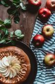 plochý ležela s uspořádány Domácí jablečný závin, čerstvá jablka s zelenými listy a plátno na dřevěný stůl