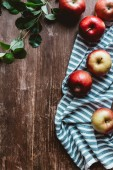 Photo flat lay with arranged ripe apples, linen and green leaves on wooden tabletop