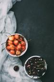 Fotografie Draufsicht von Süßkirschen in Schalen auf schwarz