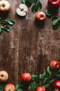 flat lay with arranged ripe apples and green leaves on wooden tabletop