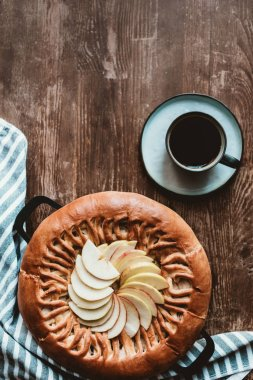 top view of homemade apple pie and cup of coffee on wooden tabletop