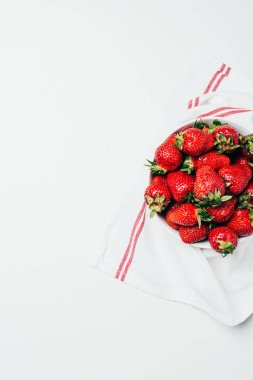 tp view of fresh ripe red sweet strawberries in bowl with towel on white