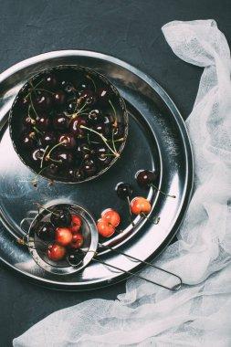 top view of fresh sweet cherries in shiny metal plate on black