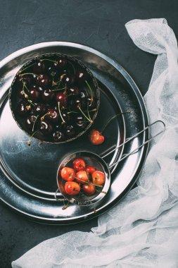 top view of fresh ripe sweet cherries in shiny metal plate