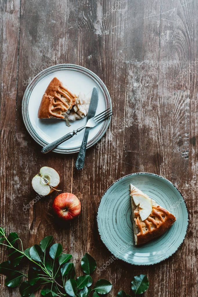 flat lay with pieces of apple pie on plates, cutlery and fresh apples arranged on wooden tabletop
