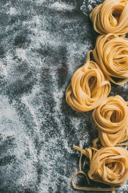 top view of raw tagliatelle pasta on table covered by flour
