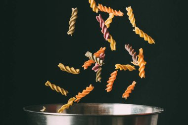 close up shot of colorful fusilli falling into pan on black background