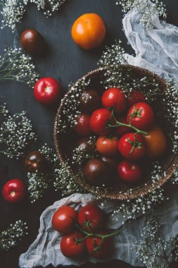 top view of fresh red tomatoes in wicker bowl with white flowers