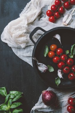 top view of red cherry tomatoes with basil leaves in frying pan on gauze on wooden background